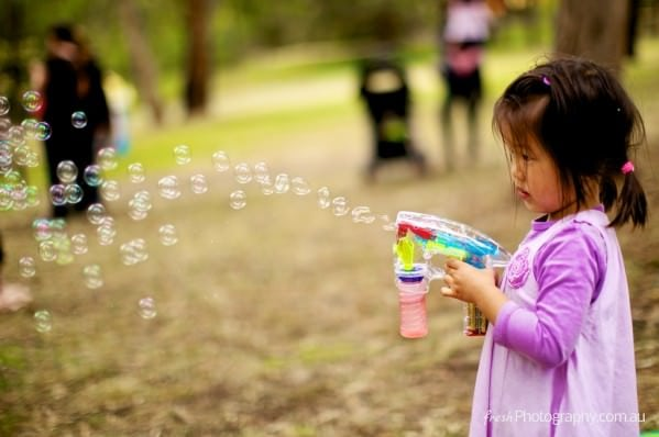 Asian kid having fun with bubble machine