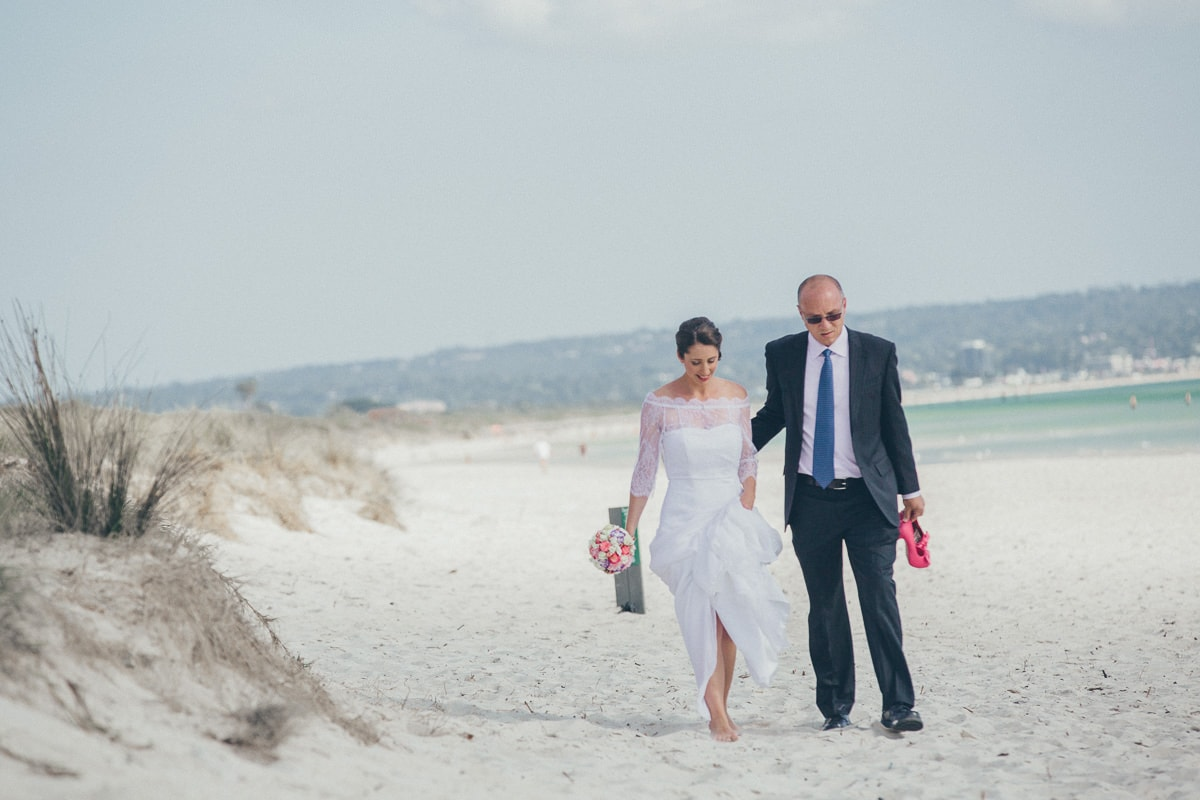 father walking the bride across the beach to the groom  waiting - photography in melbourne