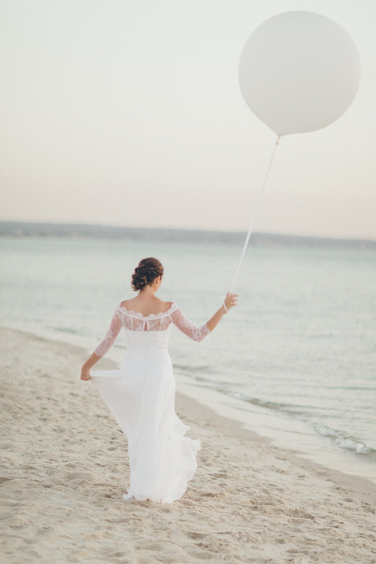 bride walking along the beach with oversized white balloon - wedding photo in melbourne - melbourne beach side brighton sandringham elwood