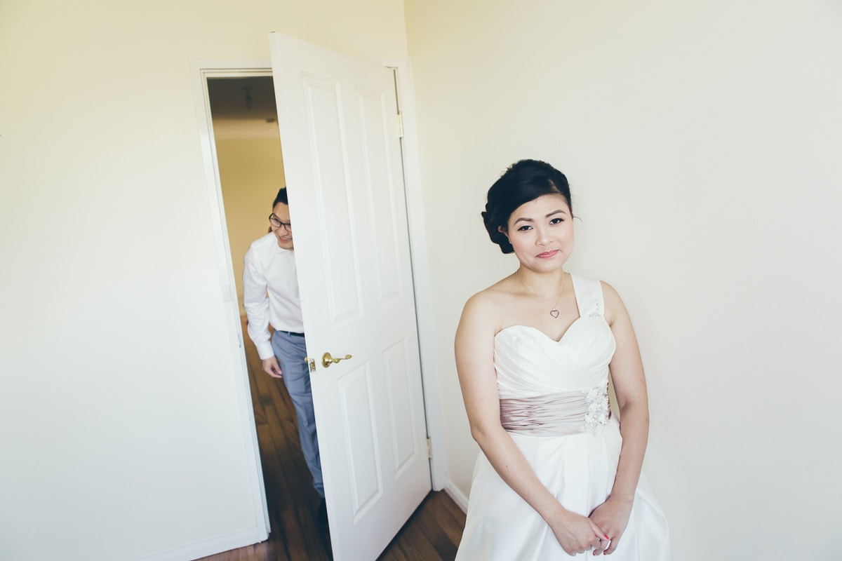 groom entering the room - bride looking out of the window