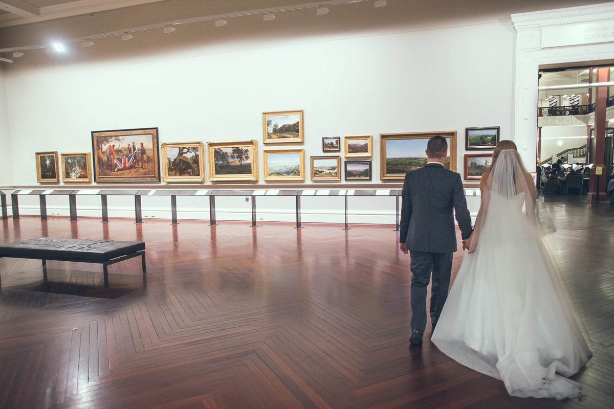 bride and groom wandering through gallery at the state library of victoria -  we love wedding photos