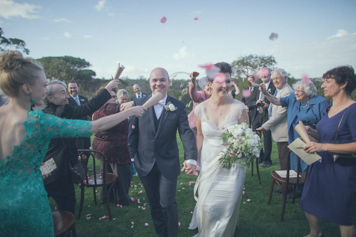 married couple leaves ceremony at barn wedding in melbourne - rose petals throwing bye guests - fun and emotion beautifully captured by melbourne photographer
