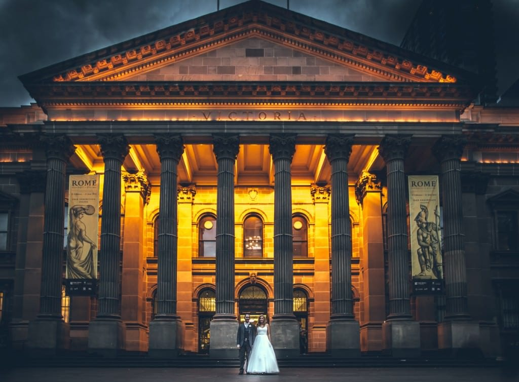 wedding package - melbourne cbd wedding photographer - state library from outside - lit up with wedding couple in front - stunning melbourne photography by professional photographer