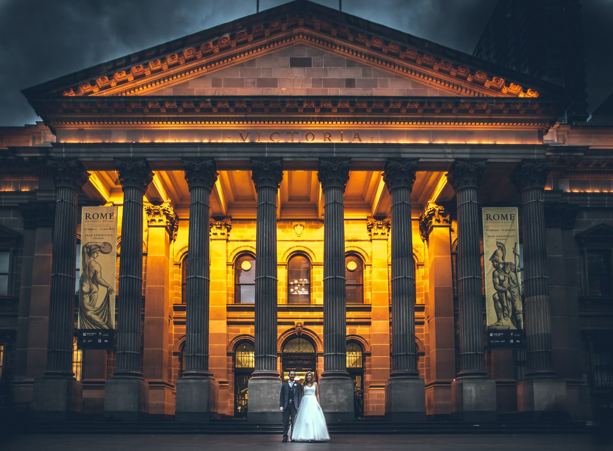 melbourne cud wedding photographer - state library from outside - lit up with wedding couple in front - stunning melbourne photography by professional photographer