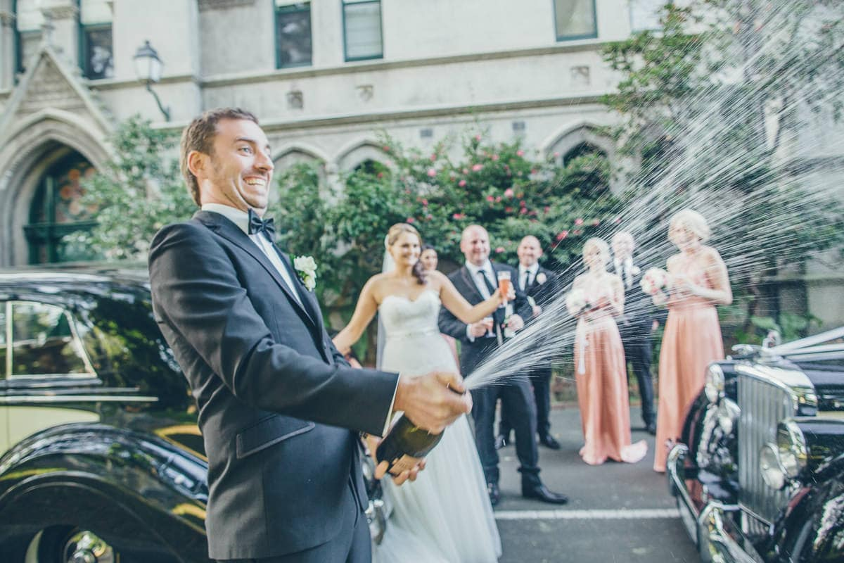 groom opening a bottle of champagne and splashing - best wedding photos - fun wedding photographer in melbourne - shot taken in kew