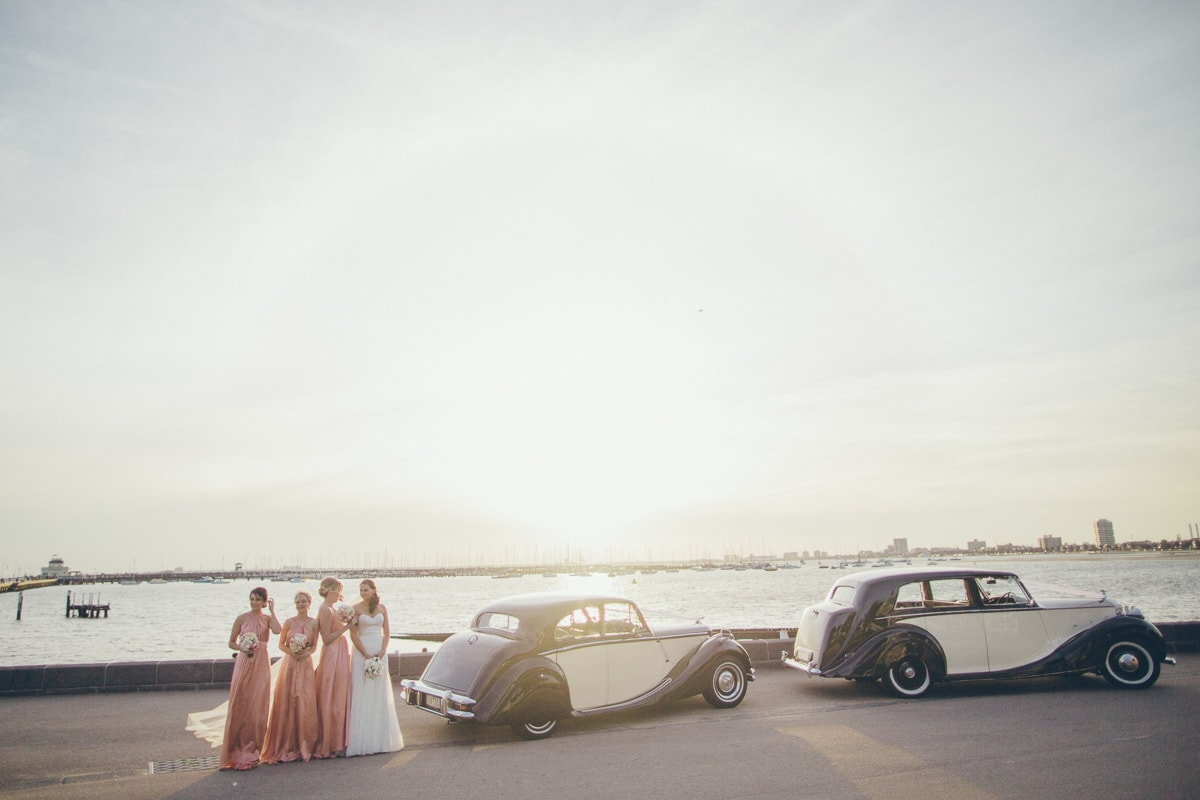 natural wedding photography - the cars arrive at the beach - st kilda pier