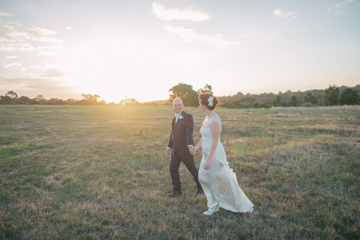 sunset wedding - couple does photoshoot in the fields - walking