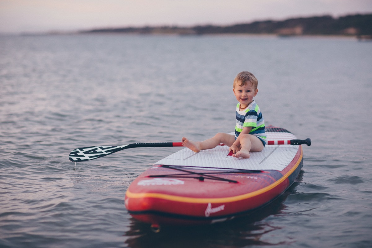 boy sitting on stand up paddle board
