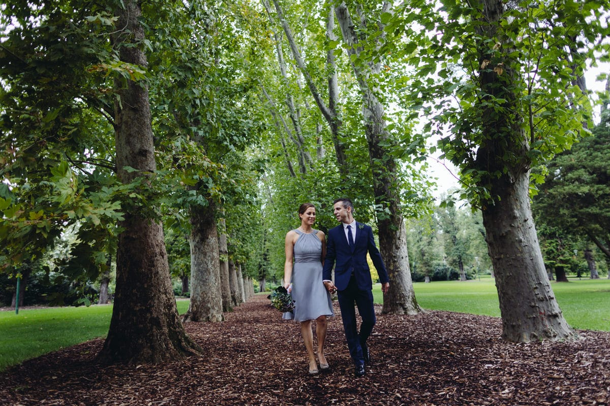 wedding couple walking through melbourne parks captured by wedding photography