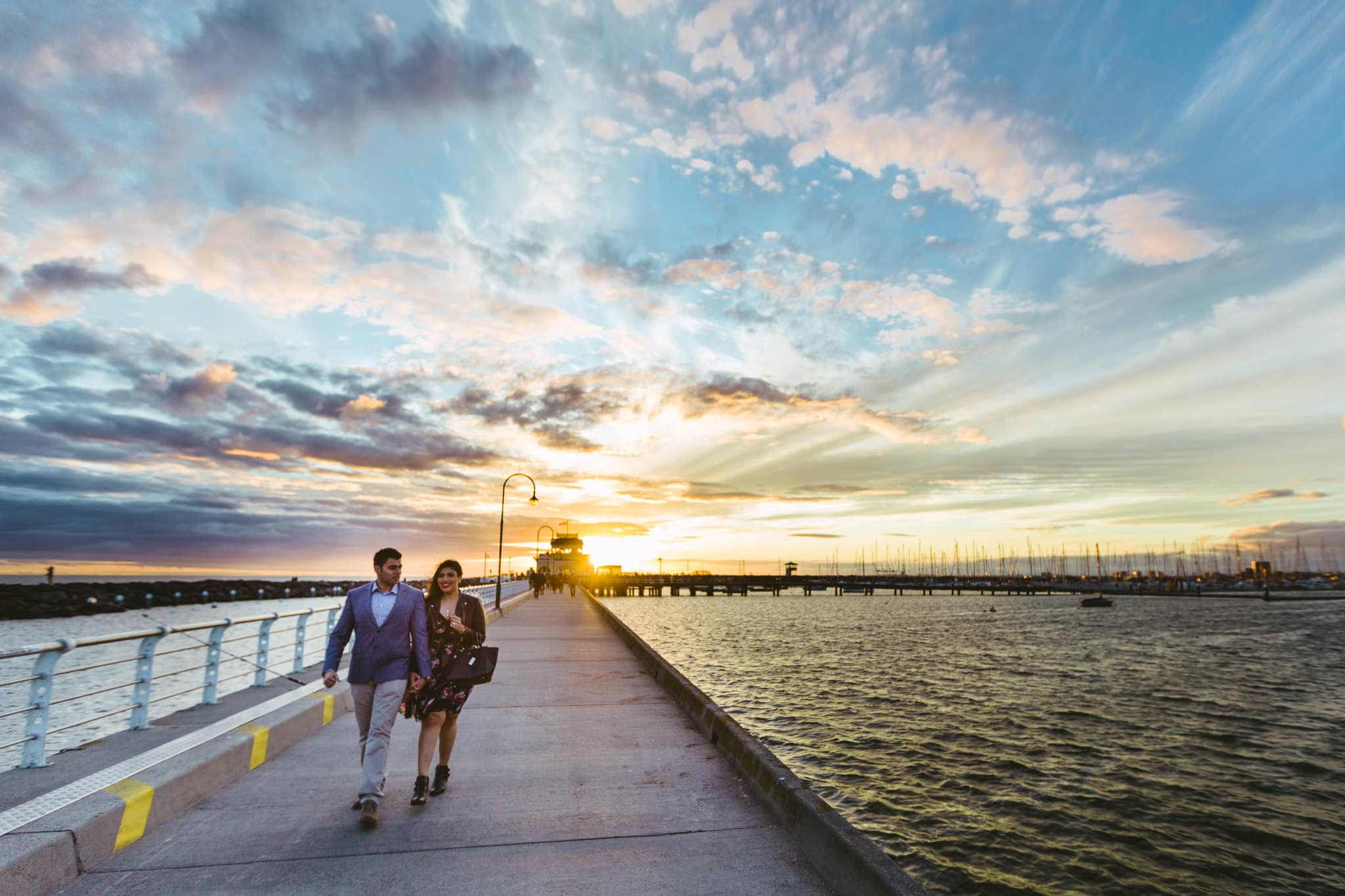 wedding couple walking down st kilda pier - surprise wedding captured by  melbourne photographer