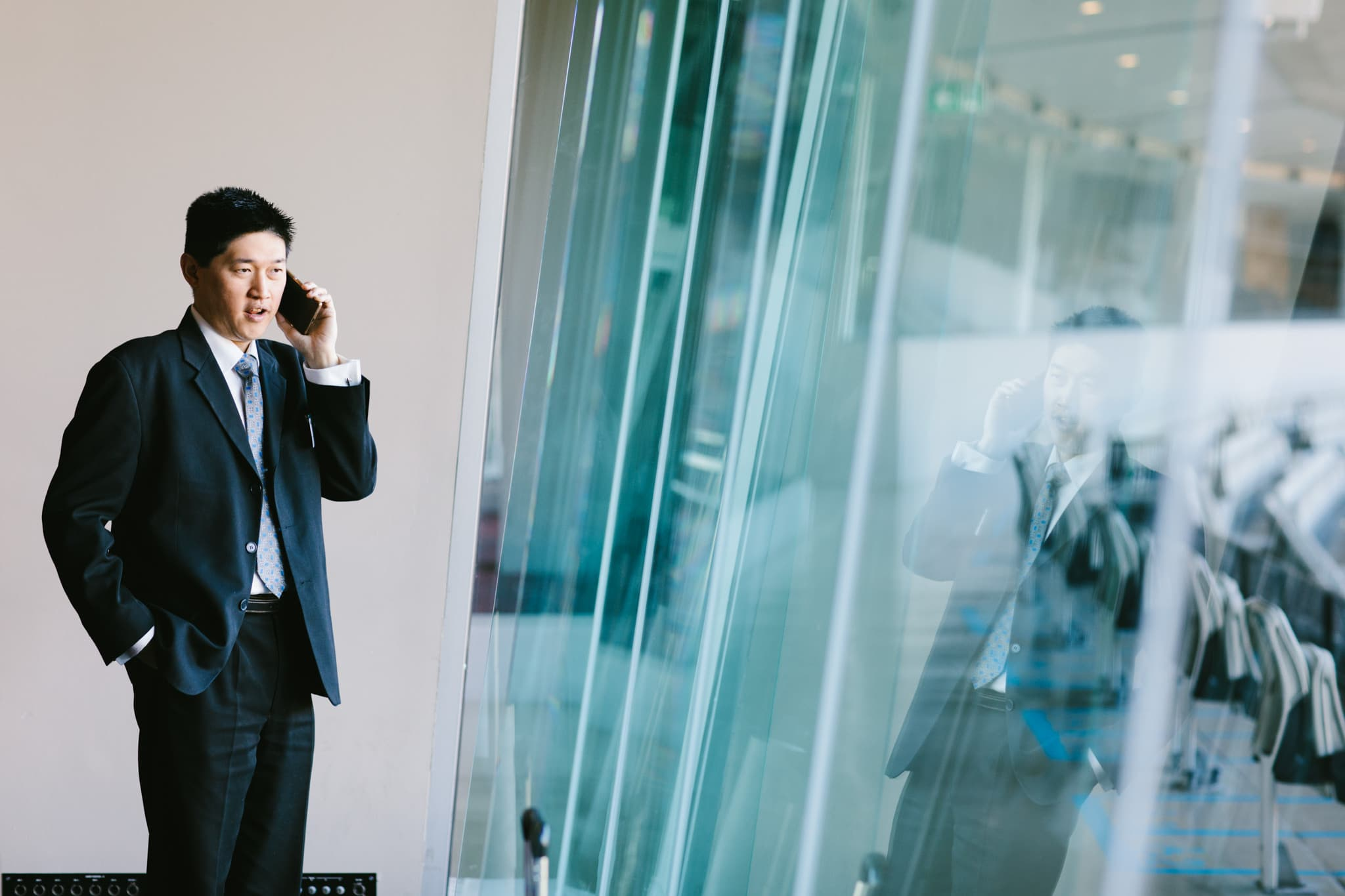 asian man on mobile phone in front of white wall and windows
