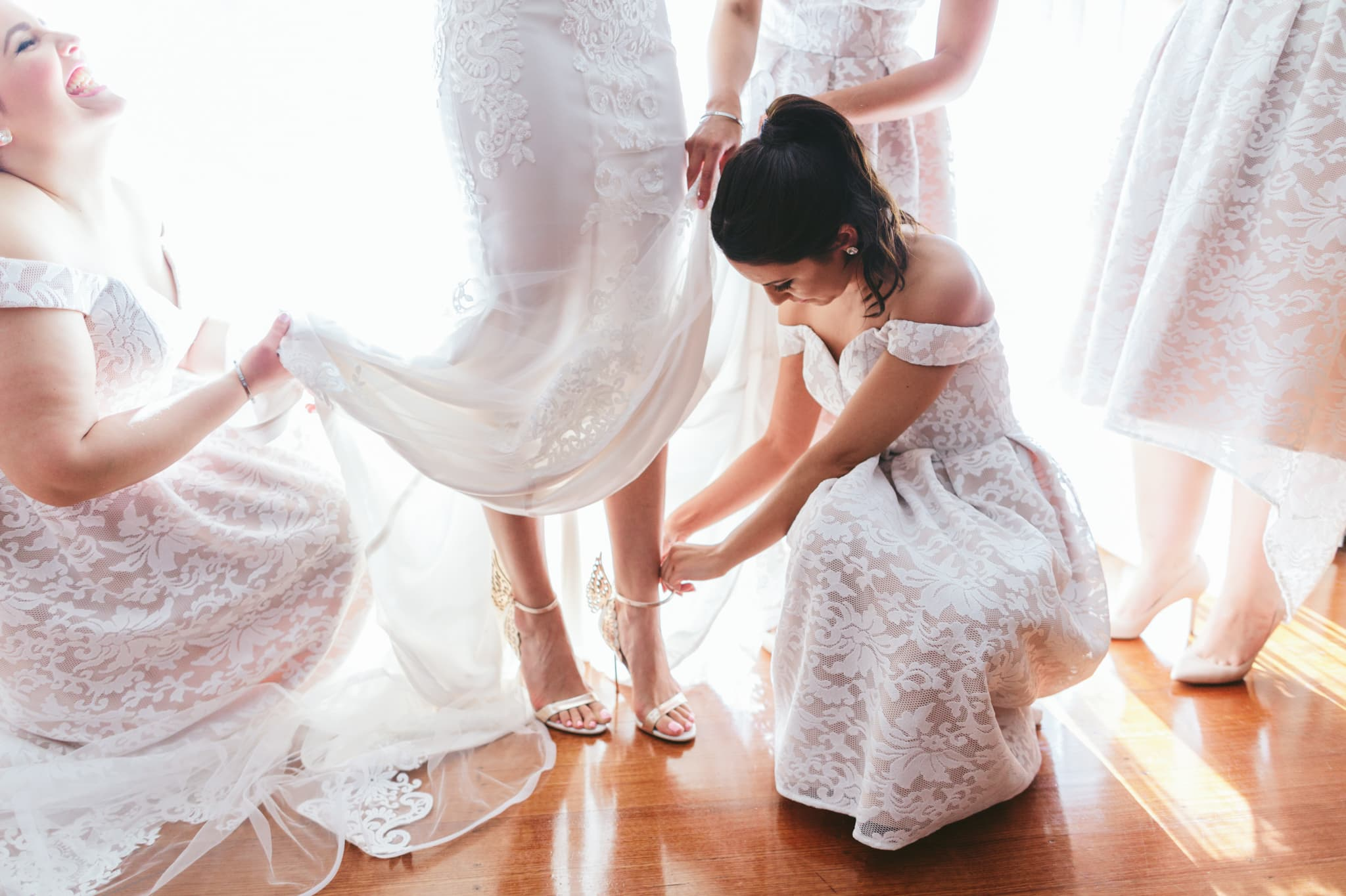 bridesmaids help the bride getting dressed - wedding photographer captures the day