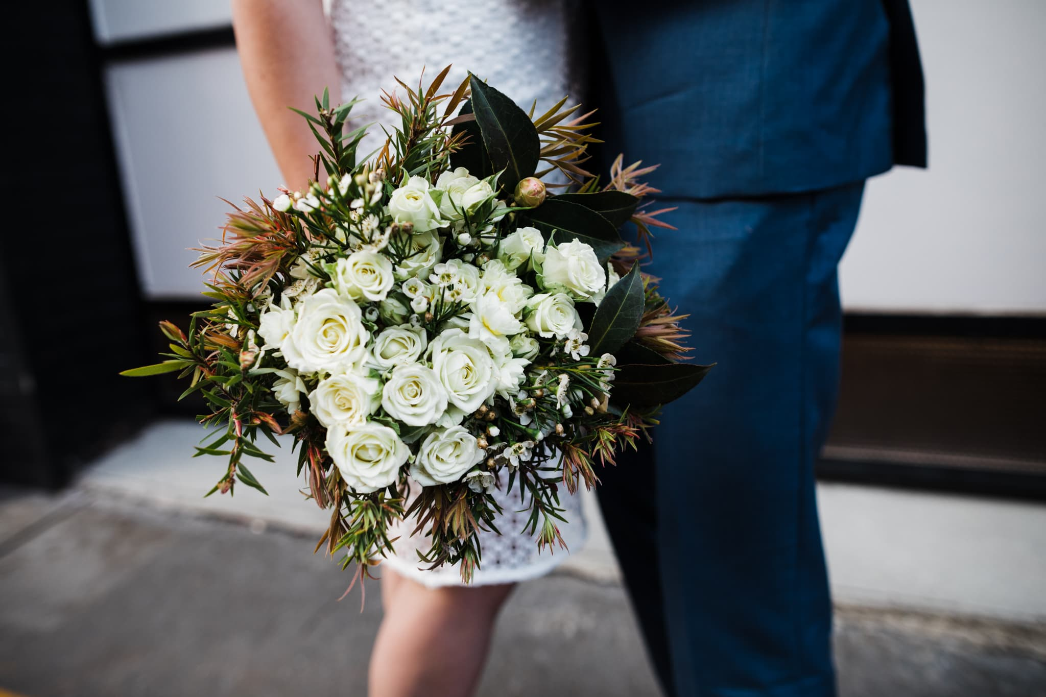 urban brideal bouquet in white - held by bride and groom - blurry