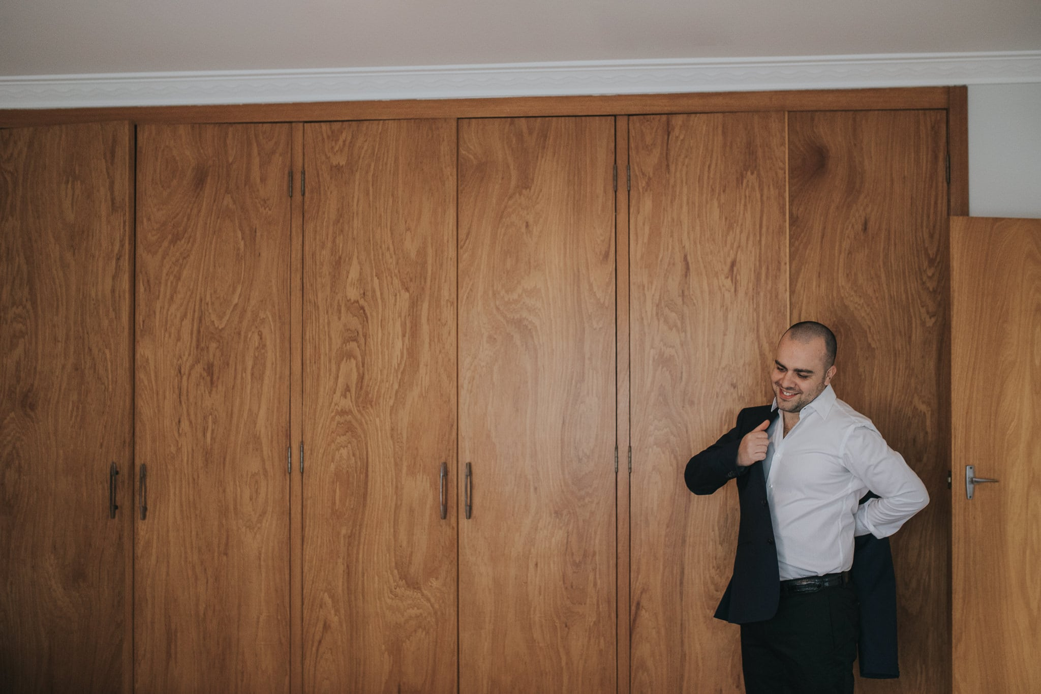 Groom getting ready - Jacket with simple background - Photo in Melbourne