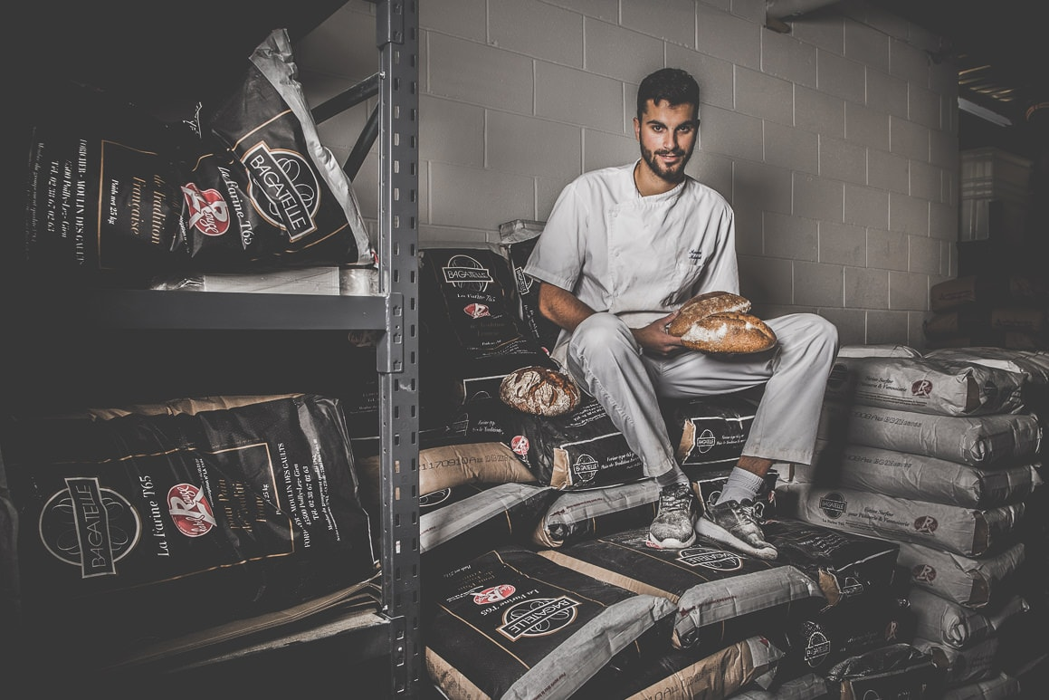 portrait photo of a baker with bread on flour bags in bakery - commercial photoshoot