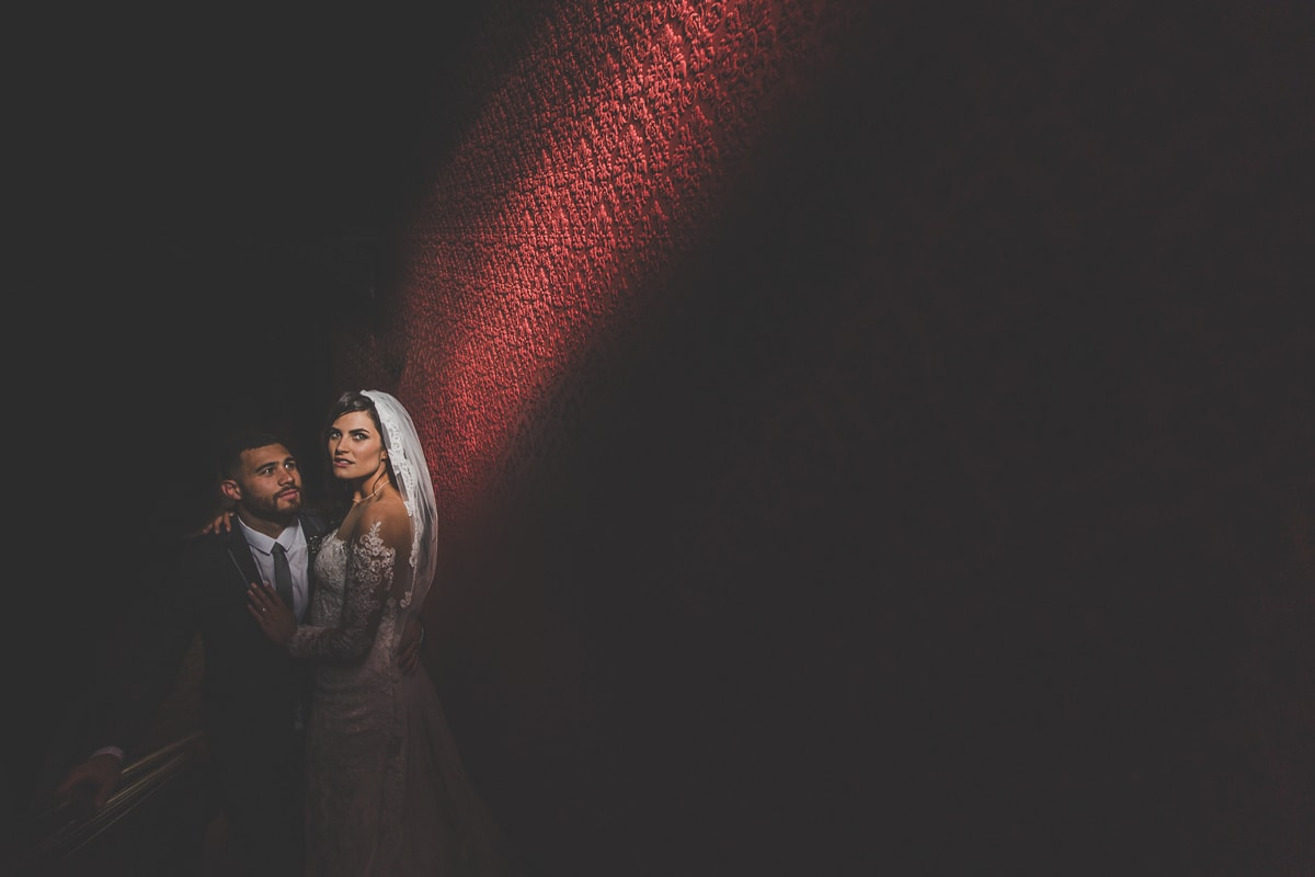 wedding photo themes - stunning mansion wedding - couple in stairway with light shining on them in a luxury melbourne wedding