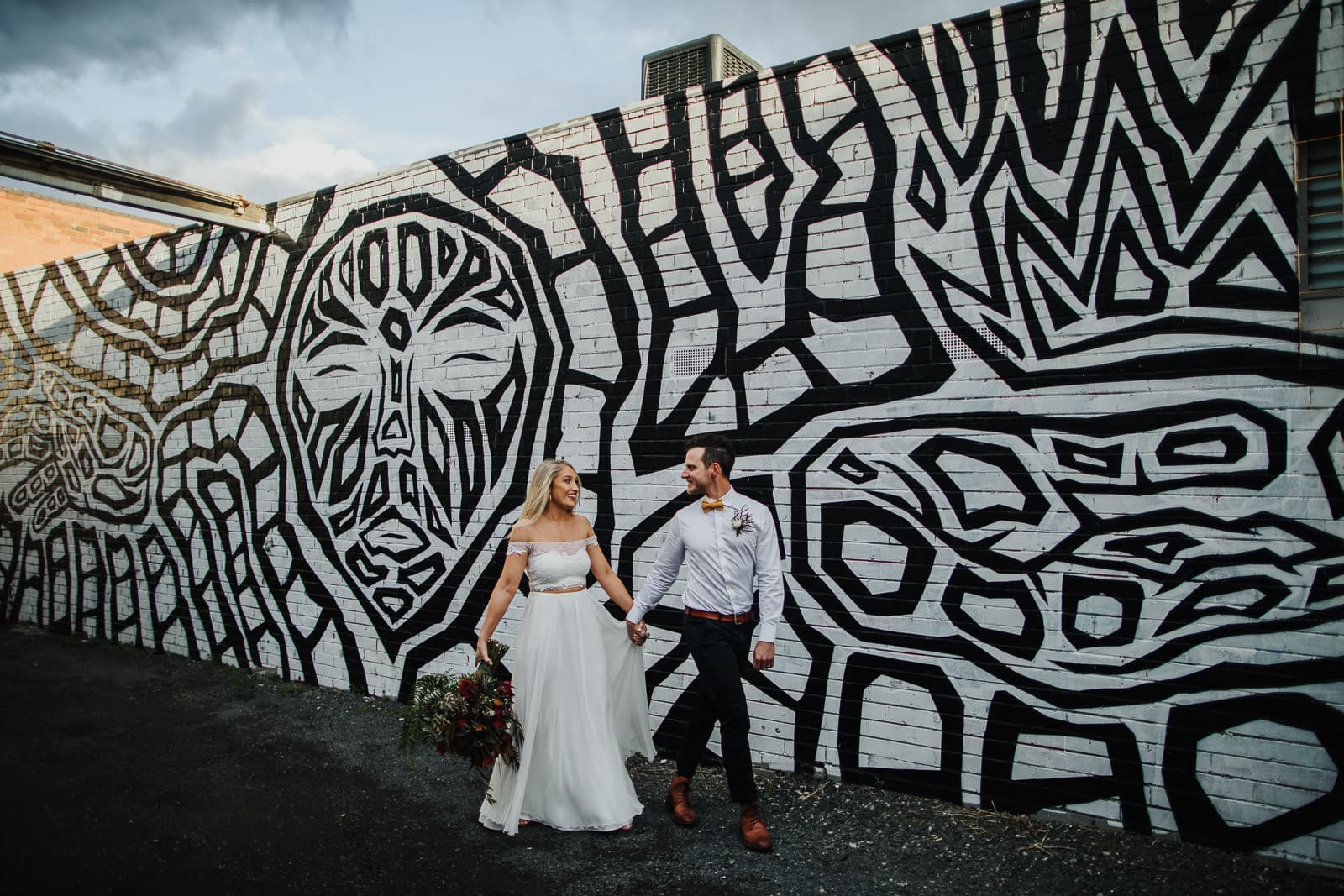 fun wedding photography - find the right photographer - Couple walking in Melbourne infront of black and white graffiti wall at fun wedding