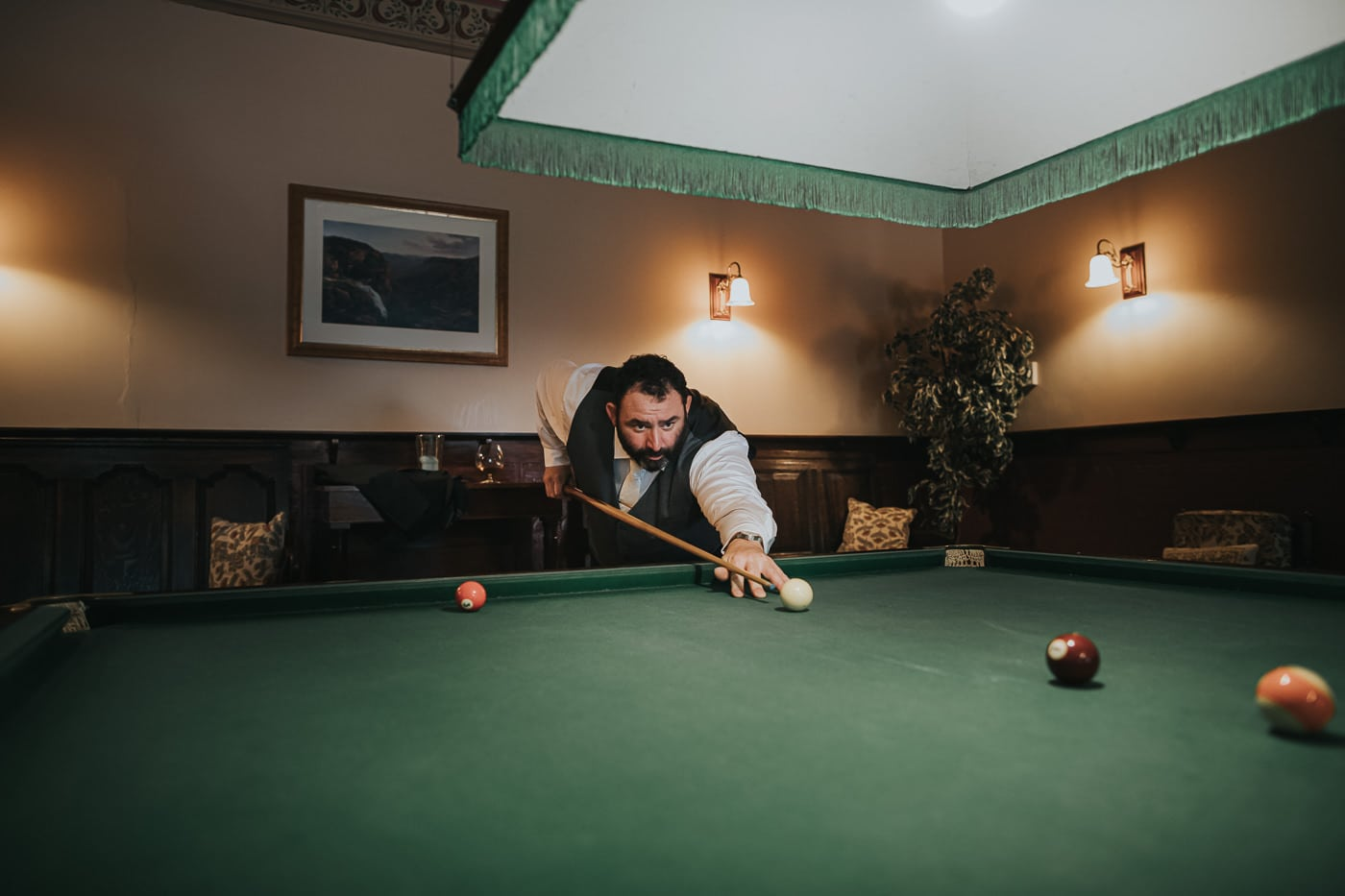 Groom playing pool billiard - before the ceremony - Photo by Flowerdale Estate Wedding Photographer