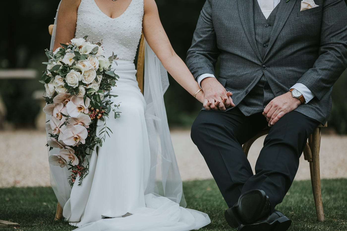 Bride and groom on chairs in garden wedding ceremony