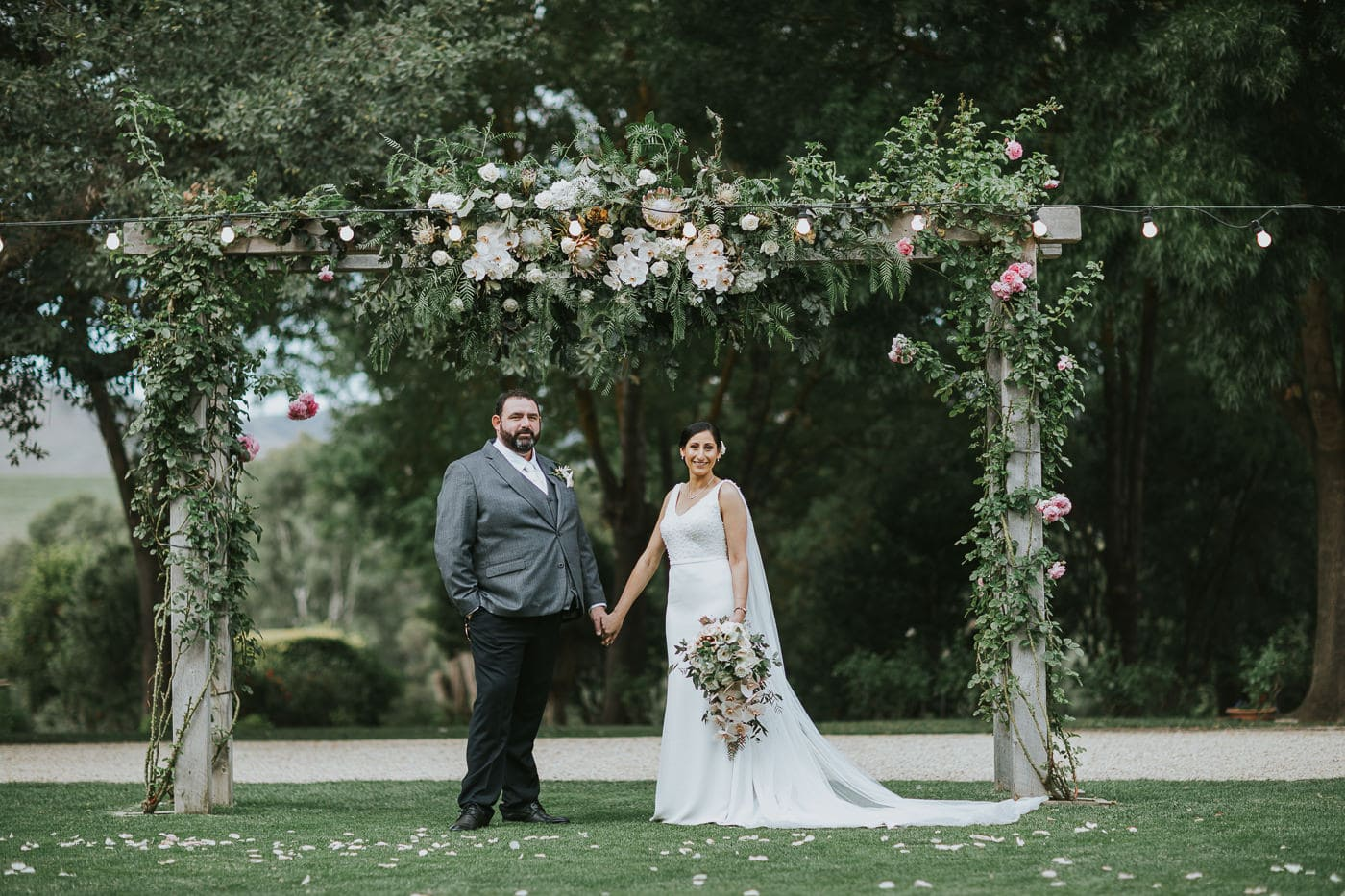 briode and groom under arbour after ceremony - Wedding venue in country victoria close to Melbourne and the Yarra Valley - Wedding Photographer captures candid and natural photos at wedding at Flowerdale Estate