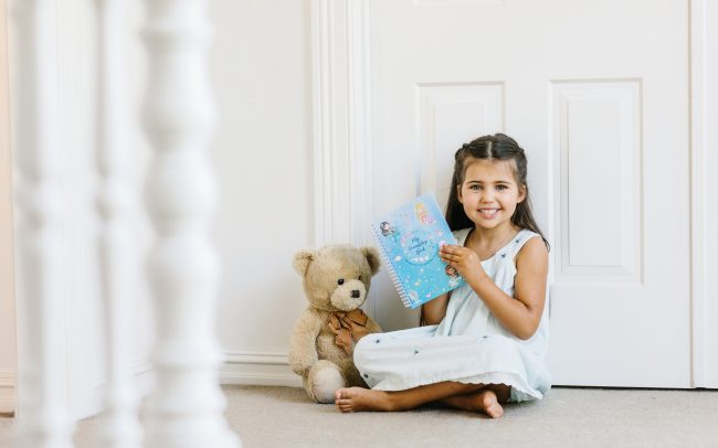 Relaxed photographer for unposed real images in Melbourne - Commercial product photos in natural settings - Child holding book with teddy bear